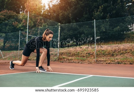 Portrait of a sportswoman stretching outdoors. Beautiful female exercising on tennis court.