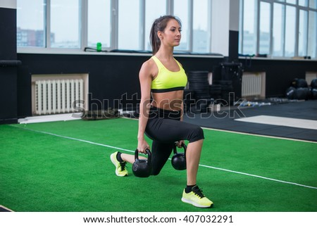 portrait of a sporty woman doing lunges with dumbbells, working out legs muscles - stock photo