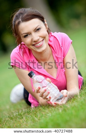 Portrait of a sporty woman with bottle of water - stock photo