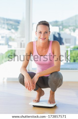 Portrait of a sporty young woman crouching on weighing scale in the gym - stock photo