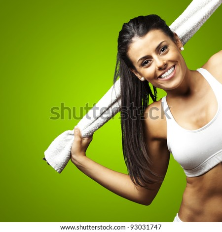 portrait of a sporty young woman with towel against a green background - stock photo
