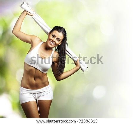 portrait of a sporty young woman with towel against a nature background - stock photo