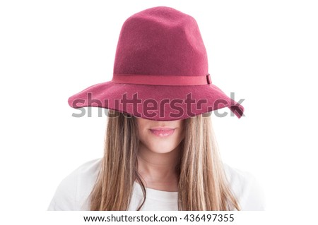 Portrait of a strange female model wearing hat and casual clothes isolated on white studio background - stock photo