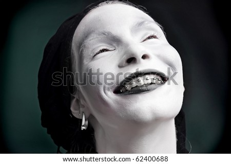 portrait of a strange woman mime with Bracket on teeth - stock photo