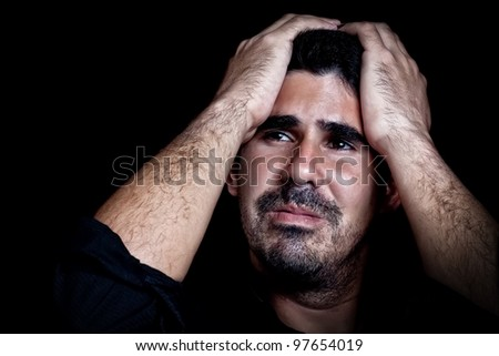 Portrait of a stressed and sad young man with a dramatic expression on a black background