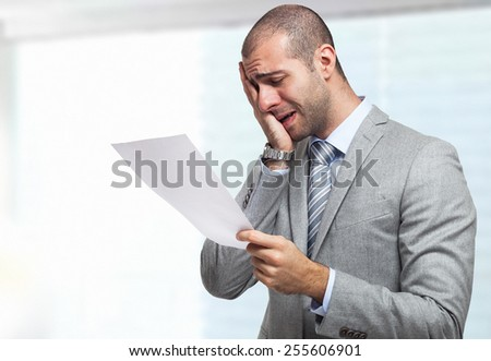 Portrait of a stressed businessman reading a document - stock photo