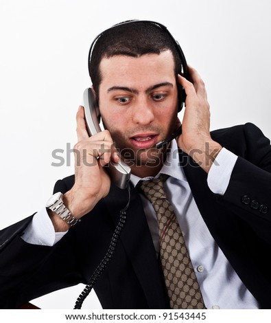 Portrait of a stressed businessman using telephone and headphones at the same time
