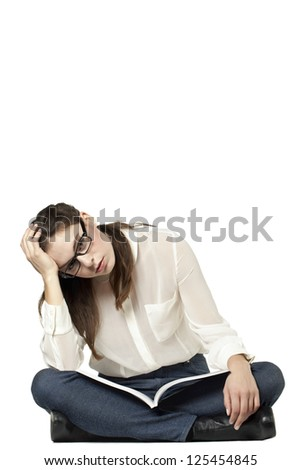 Portrait of a stressed female sitting in a white background with book on her lap - stock photo