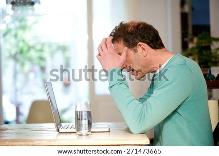 Portrait of a stressed man sitting at desk looking at laptop - stock photo