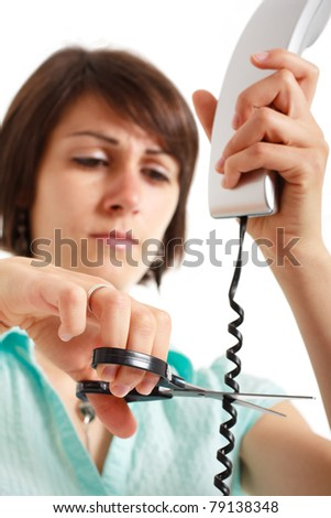 Portrait of a stressed woman cutting a telephone cable - stock photo