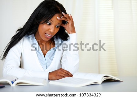 Portrait of a stressed young black woman studying at soft colors composition - stock photo