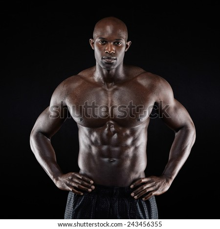 Portrait of a strong afro-american man showing off his physique against black background. Shirtless male model with his hands on hips. - stock photo