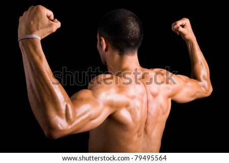Portrait of a strong back of a young muscular man against dark background - stock photo