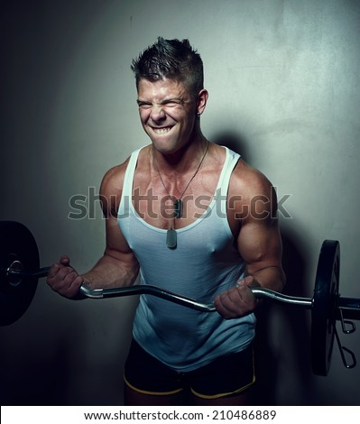 Portrait of a strong guy doing exercises with barbell - stock photo