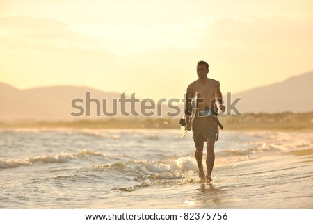 Portrait of a strong young  surf  man at beach on sunset in a contemplative mood with a surfboard - stock photo