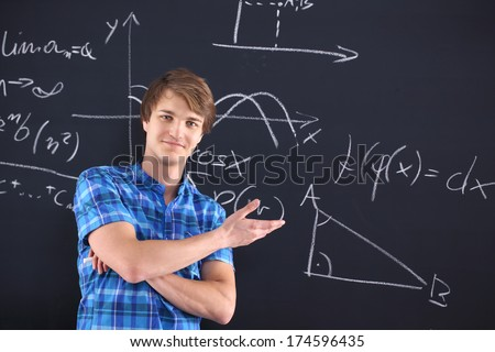 Portrait of a student at the blackboard background with patterns. Mathematics, physics, chemistry-student at the blackboard - stock photo
