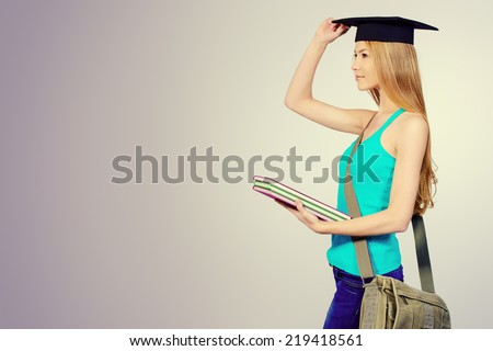 Portrait of a student girl in academic hat standing with books and purposefully looking forward. Copy space. - stock photo