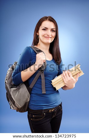 Portrait of a student girl with backpack and books on blue background