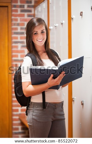Portrait of a student holding a book in a corridor