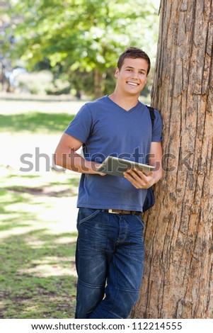 Portrait of a student leaning against a tree while using a touch pad in a park - stock photo