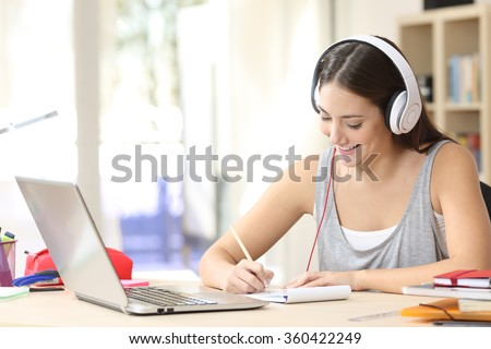 Portrait of a student learning on line with headphones and laptop taking notes in a notebook sitting at her desk at home - stock photo