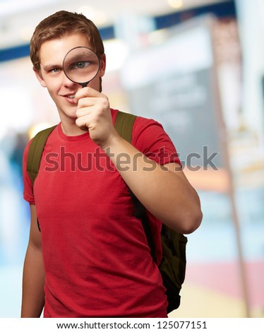 Portrait Of A Student Looking Through Magnifying Glass, Outdoor - stock photo