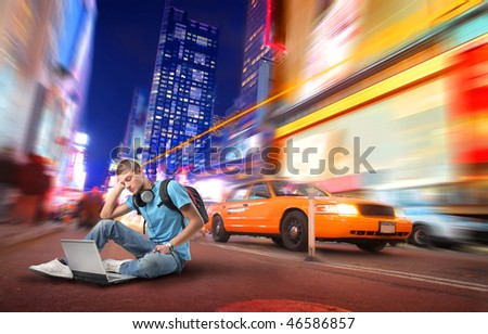 Portrait of a student sitting in the middle of a city street and using a laptop - stock photo