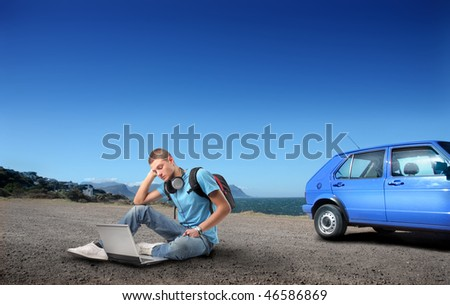 Portrait of a student sitting on the asphalt in front of a seascape and using a laptop - stock photo