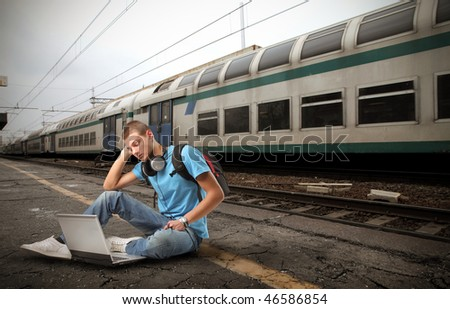 Portrait of a student sitting on the platform of a train station and using a laptop - stock photo