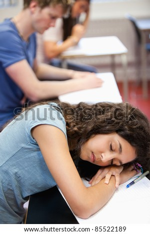 Portrait of a student sleeping on her desk in a classroom - stock photo