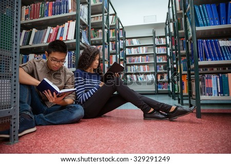 Portrait of a students sitting on the floor and reading books in library - stock photo