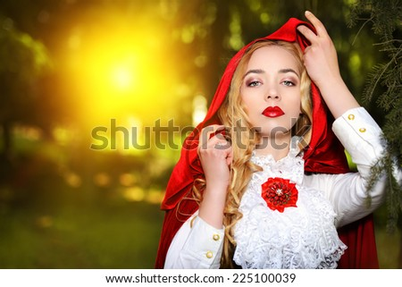 Portrait of a stunning blonde lady in  old-fashioned dress and red cloak in a fairy forest. - stock photo