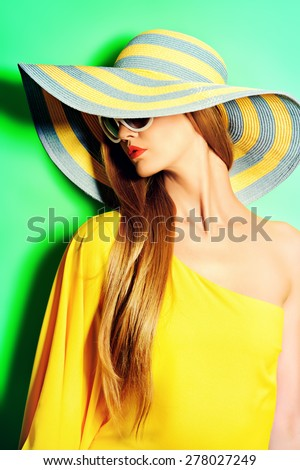 Portrait of a stunning fashionable lady in bright yellow dress posing over  green background. Beauty, fashion concept. Colors of summer. - stock photo