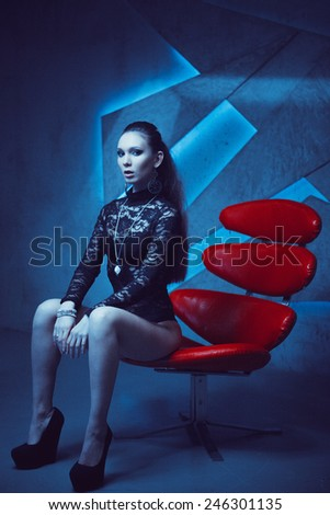 Portrait of a stunning fashionable model sitting in a red chair in modern style. - stock photo