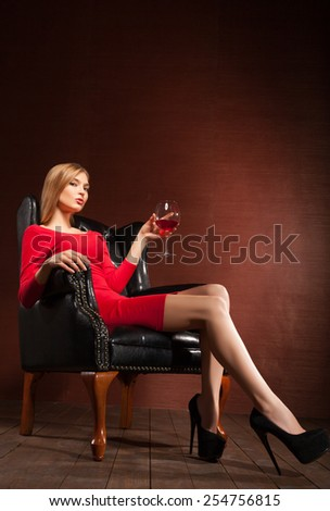 Portrait of a stunning fashionable model sitting in an armchair with wine glass. Business, elegant businesswoman. Interior, furniture. - stock photo