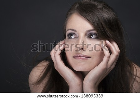 Portrait of a stunning young brunette woman resting her chin on her hands and looking off to the left of the frame with a pensive expression, head and shoulders on a dark backgorund