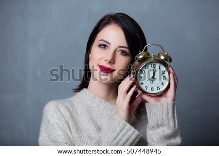 Portrait of a style brunette woman with alarm clock on grey background