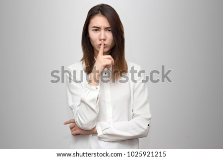 Portrait of a stylish and calm young woman with dark hair and white shirt, looking into the camera, asking for silence, pressing her finger to her lips on the grey background