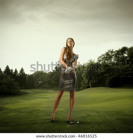 Portrait of a stylish beautiful woman holding a golf club on a green meadow - stock photo