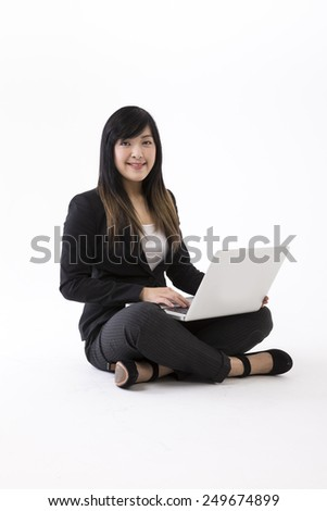 Portrait of a stylish Chinese Businesswoman using a laptop. Isolated on white background. Asian brunette female model. - stock photo