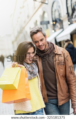 Portrait of a stylish couple doing their shopping in the city center The grey hair man with beard is wearing a leather coat and the woman a yellow top and two shopping bags, they also have scarfs - stock photo