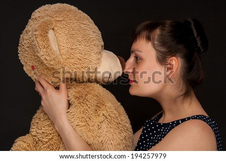 portrait of a stylish expressive woman with teddy bear in studio