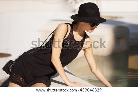 Portrait of a stylish fashionable young brunette beauty outdoors in summer.
