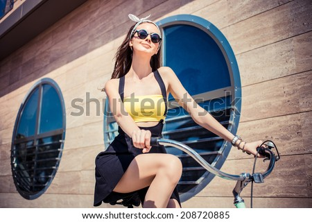 Portrait of a stylish girl hipster riding a  cruiser bicycle against the background of the building with round windows - stock photo