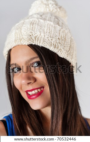 Portrait of a stylish girl wearing winter wool hat, isolated on gray background