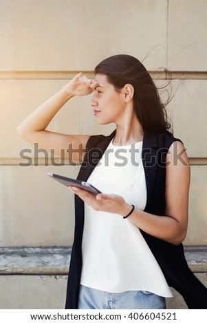 Portrait of a stylish hipster girl is using digital tablet for navigation in urban setting, attractive latin woman wanderer is searching Sight street though touch pad map during vacations abroad - stock photo