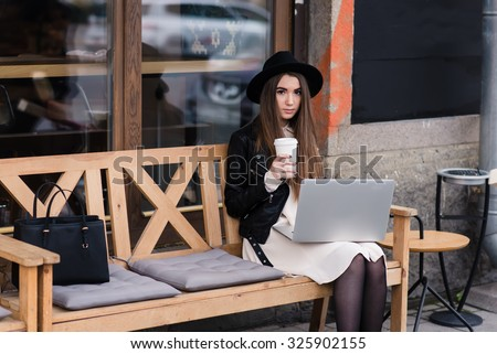Portrait of a stylish hipster girl posing while sitting with net-book and cup of coffee on a bench on the street, young beautiful woman working on portable computer during rest after walking outdoors - stock photo
