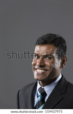 Portrait of a stylish Indian businessman standing in front of a dark grey background.