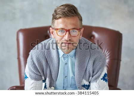 Portrait of a stylish intelligent man with glasses stares into the camera, good view, small unshaven, charismatic, blue shirt, gray sweater, sitting on a brown leather chair - stock photo