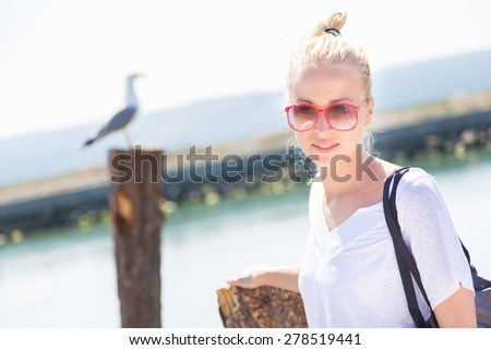 Portrait of a stylish lady strolling on the beach. Summertime feeling. - stock photo